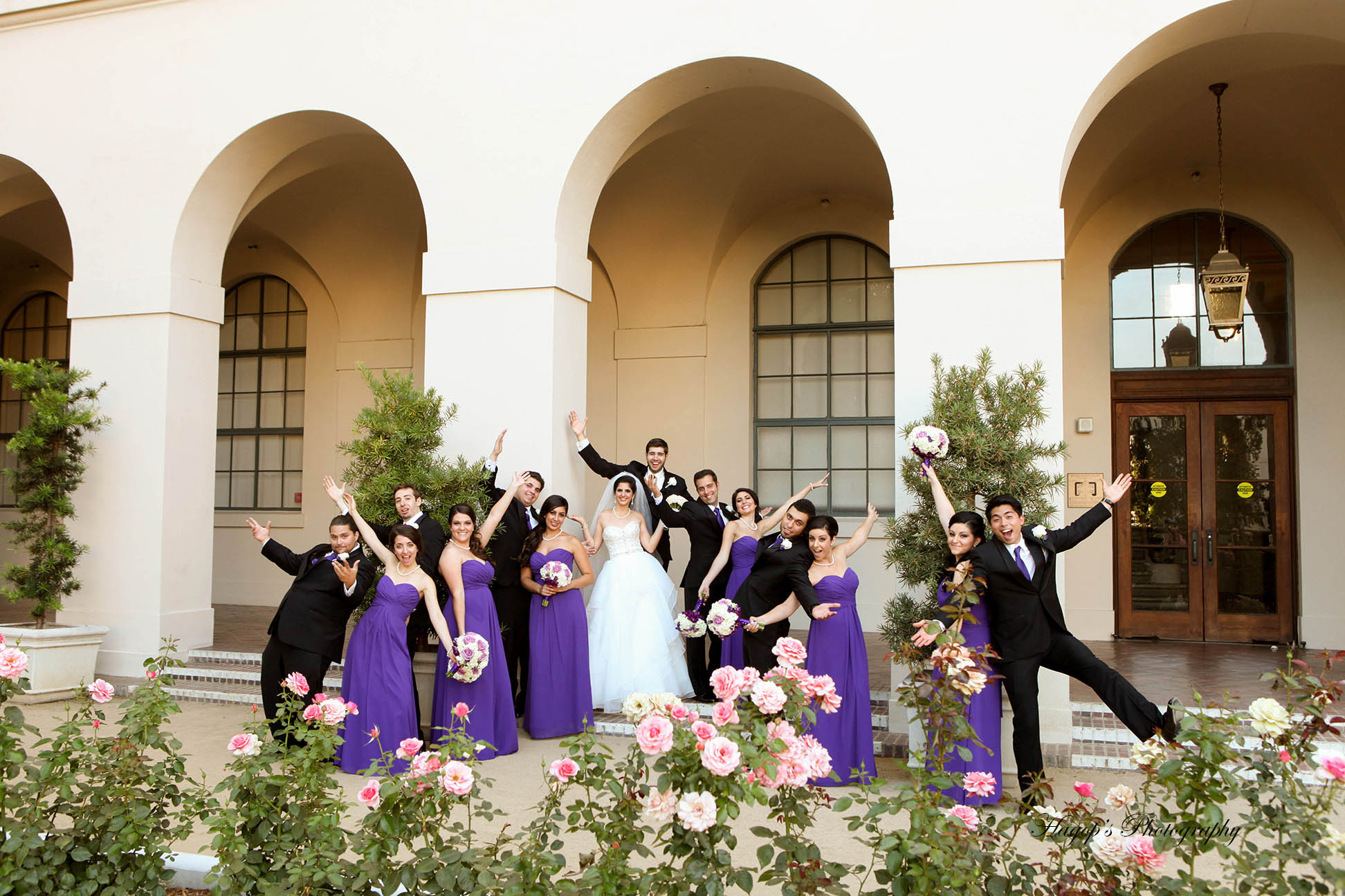 bridal party posing for the camera with hands in the air