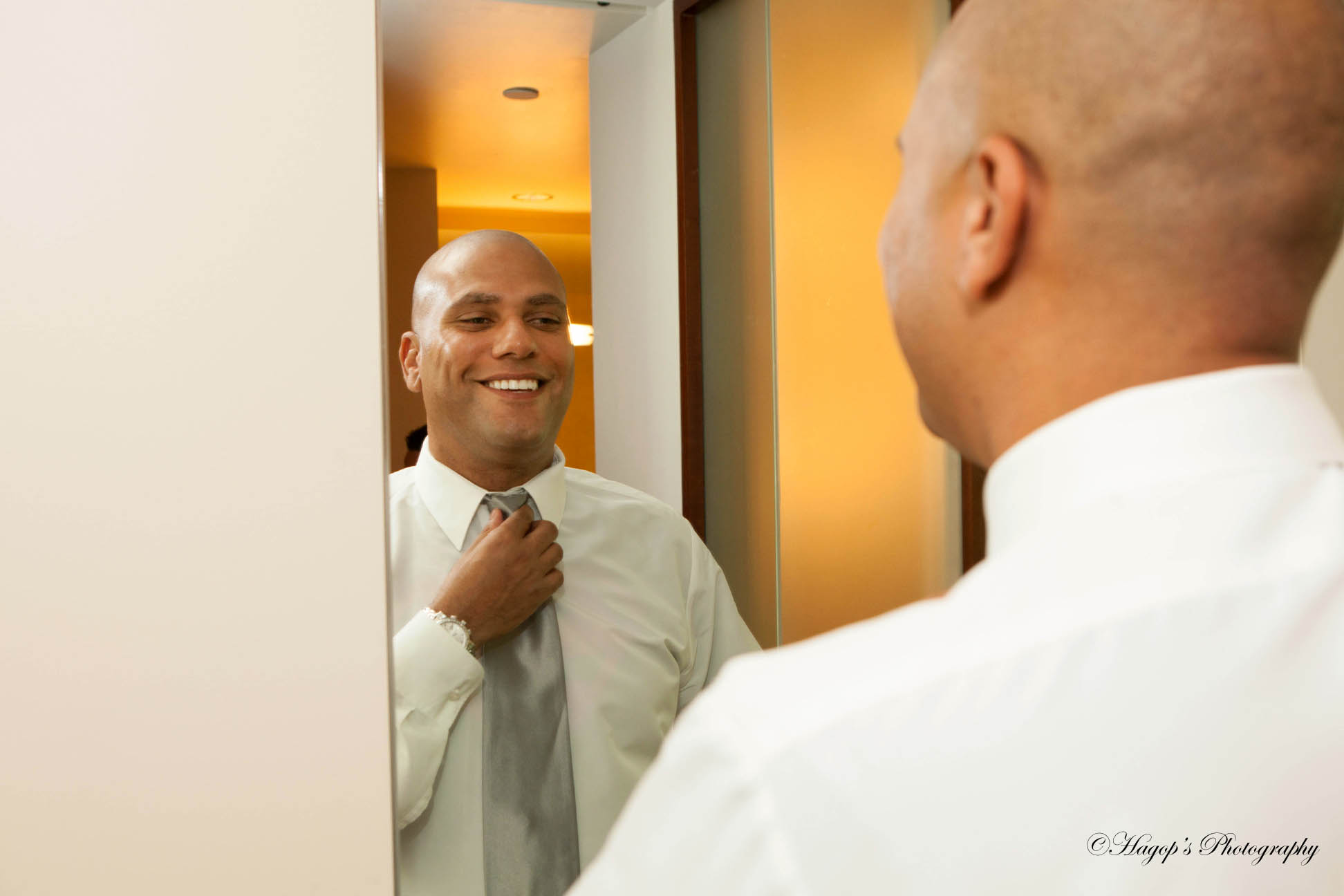 groom getting ready by fixing his tie