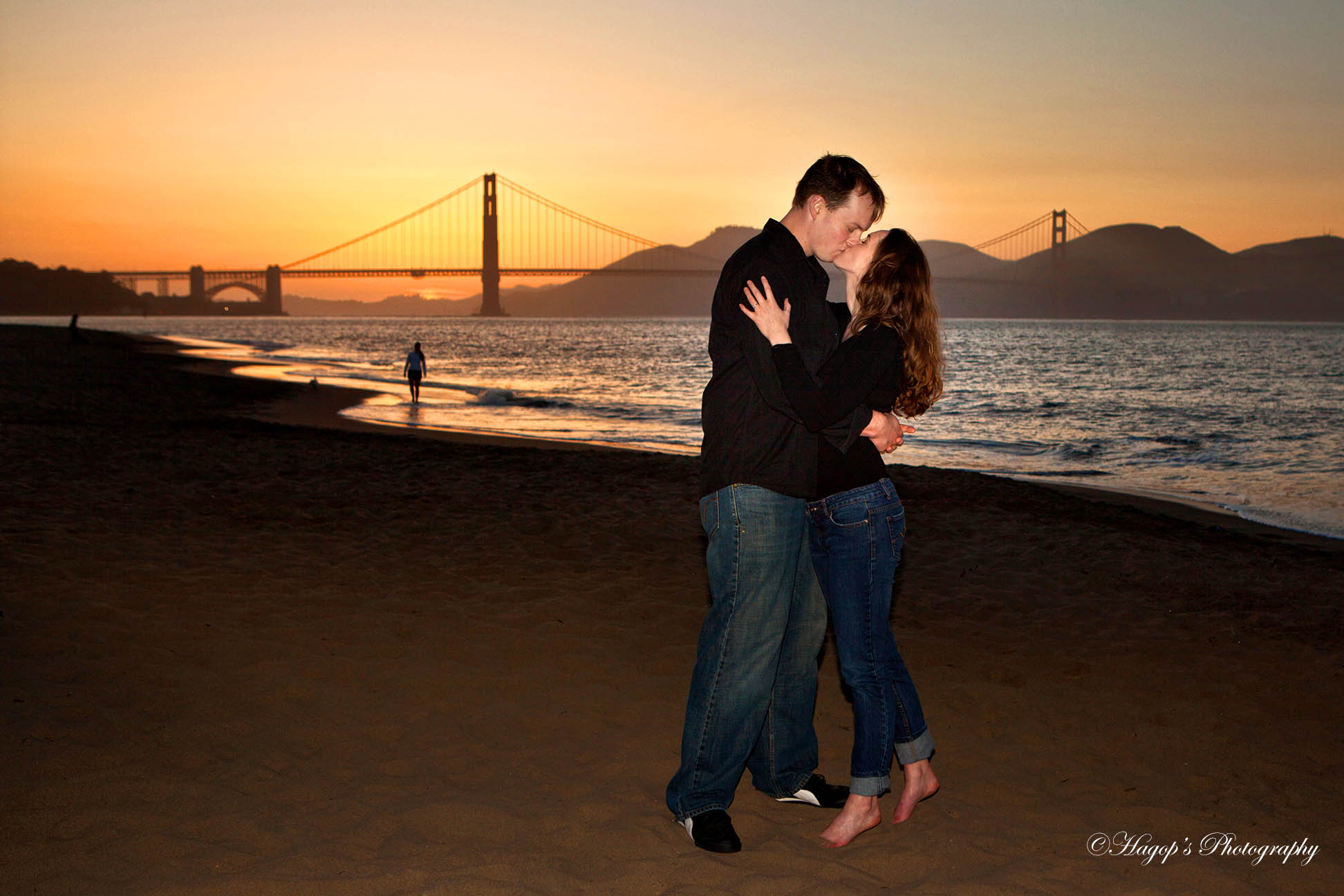 engaged couple kissing at crissy field with the golden gate in the background at sunset