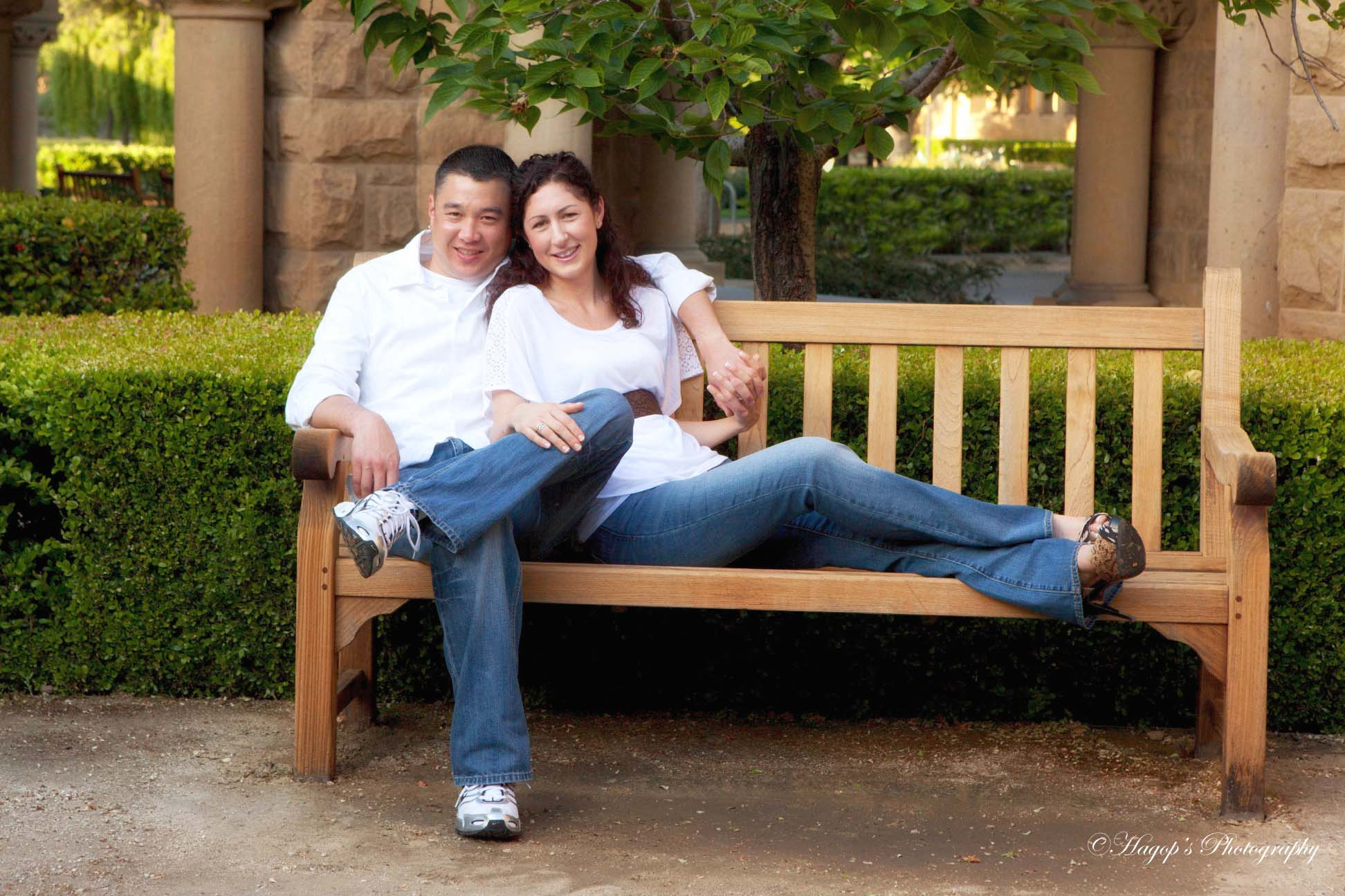 engaged couple sitting on a bench posing for the camera