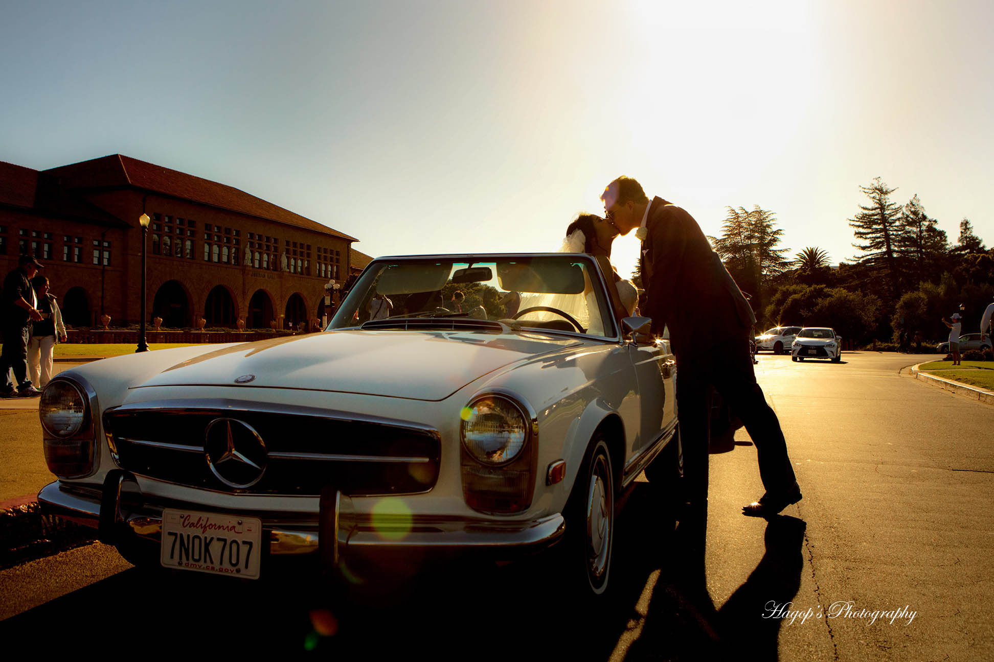 couple kissing by their classic car
