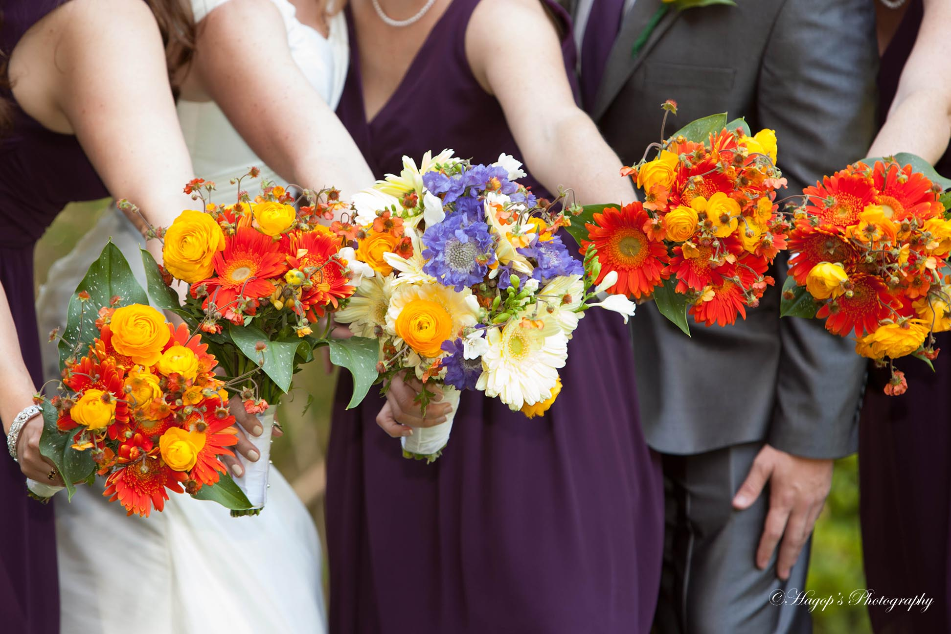 bridesmaids point their bouquets to the camera