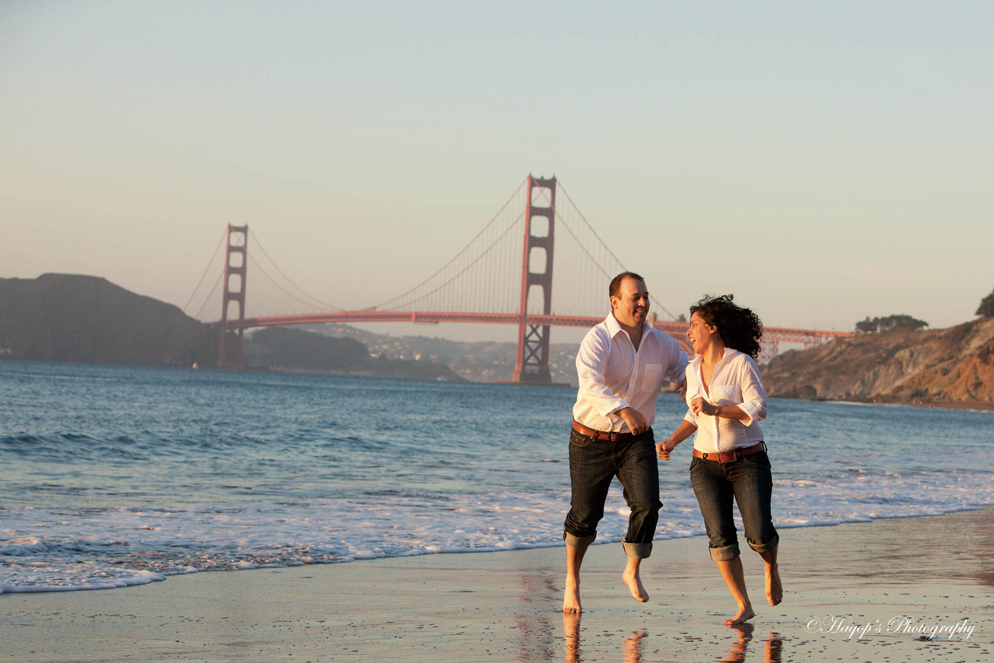 groom runs after his fiancée at baker beach with the golden gate bridge in the background