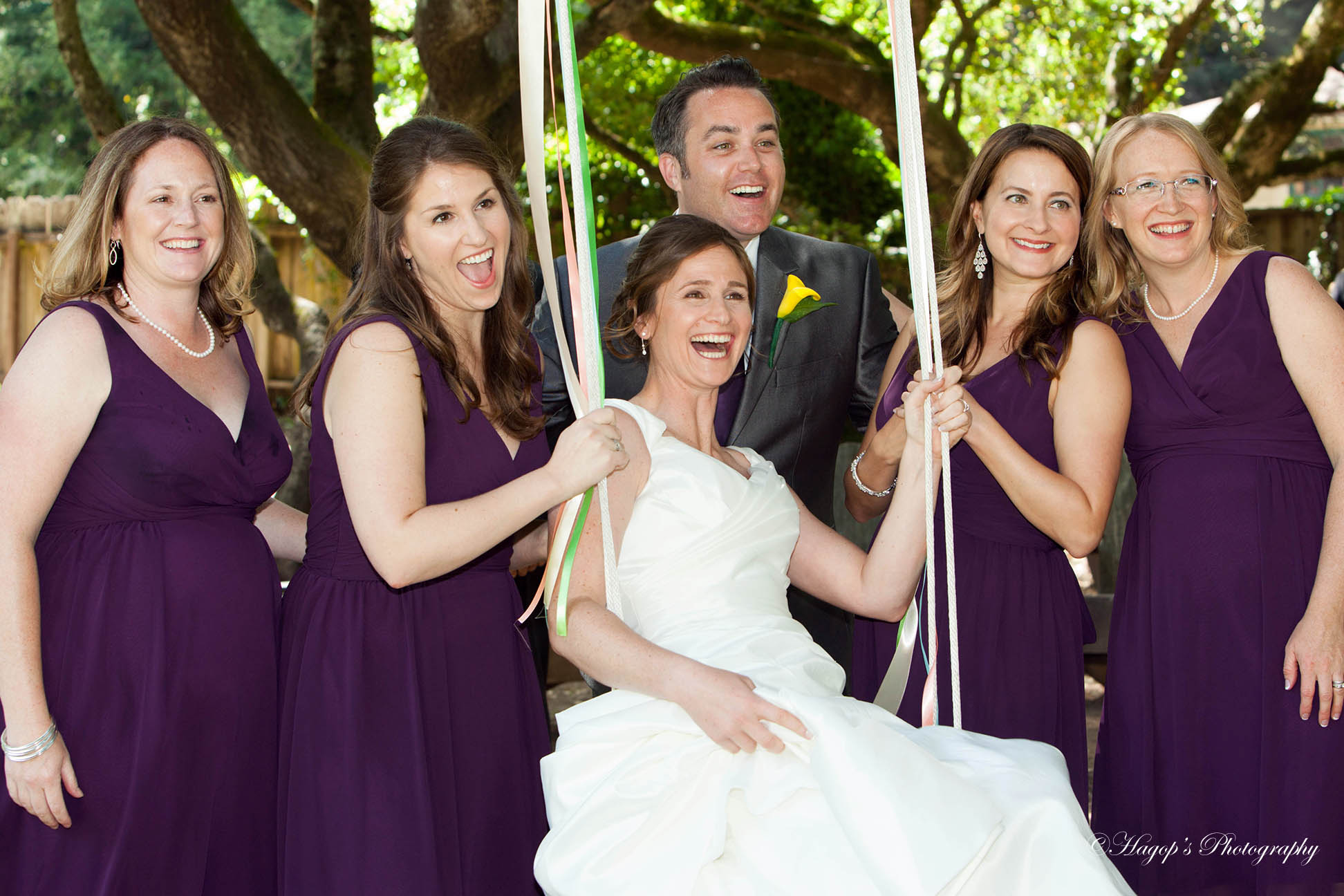 bride with her bridal party on the swing
