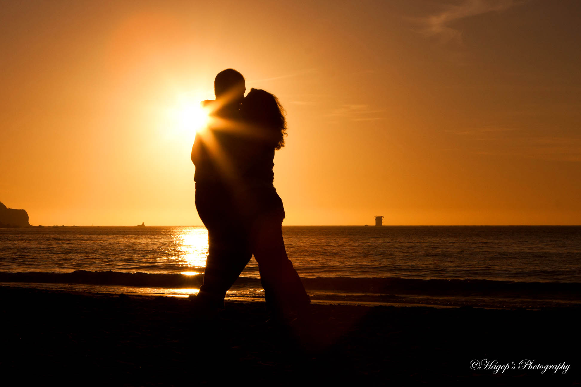 sunset romantic engaged couple kissing at baker beach