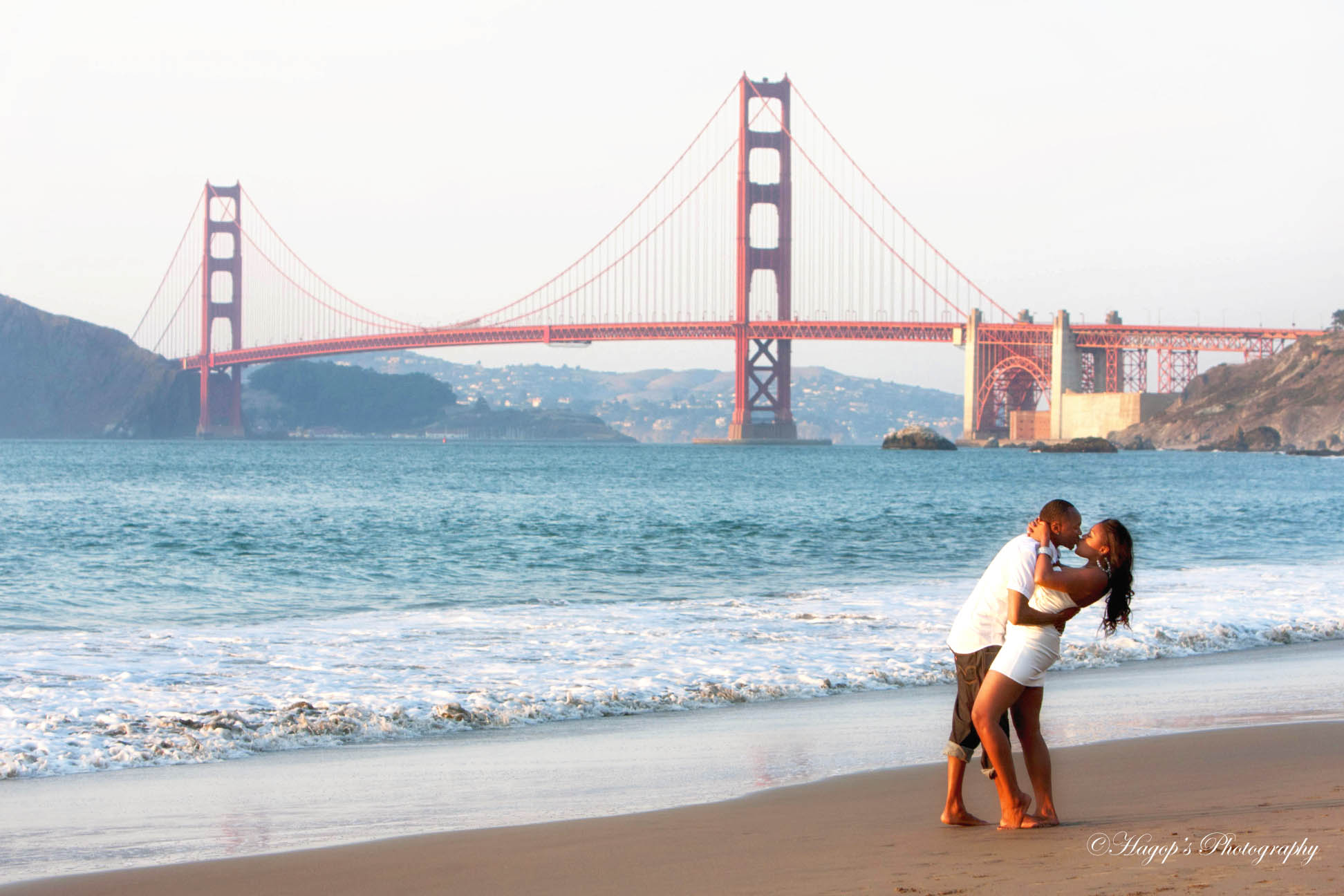 engaged couple kissing with the golden gate bridge in the background