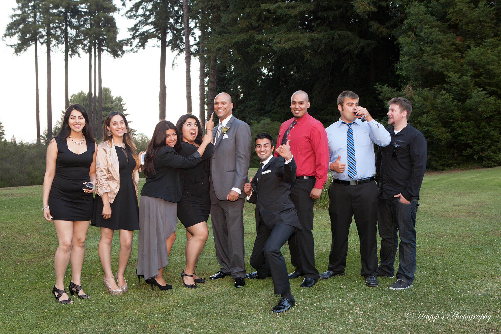 a fun photo of guests posing with the groom
