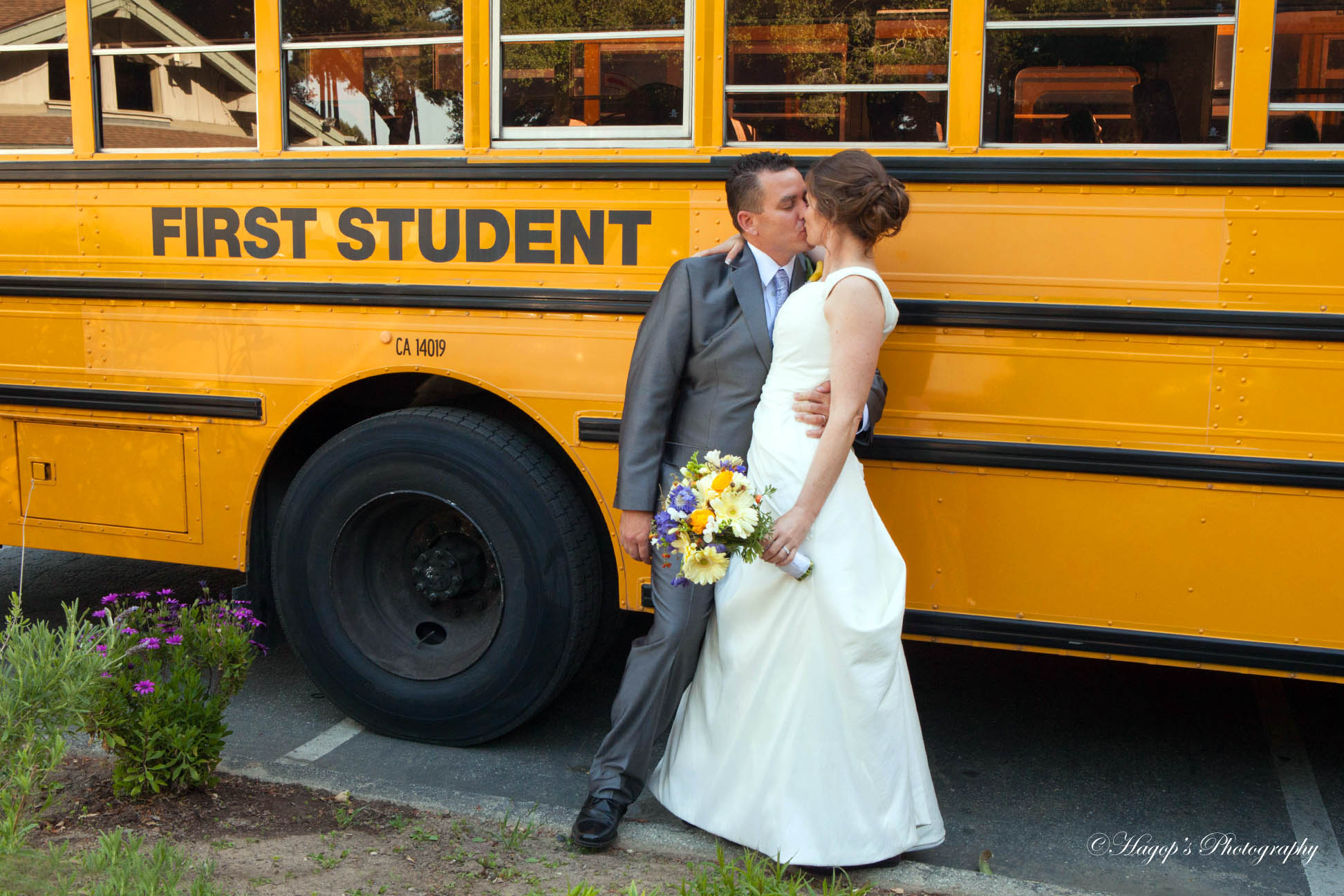 bride and groom kissing in front of the school bus