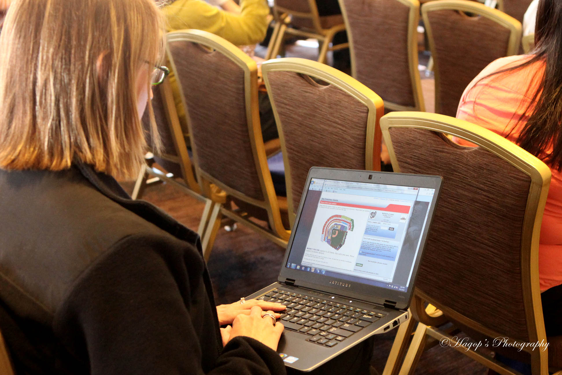 female attendee typing on her laptop