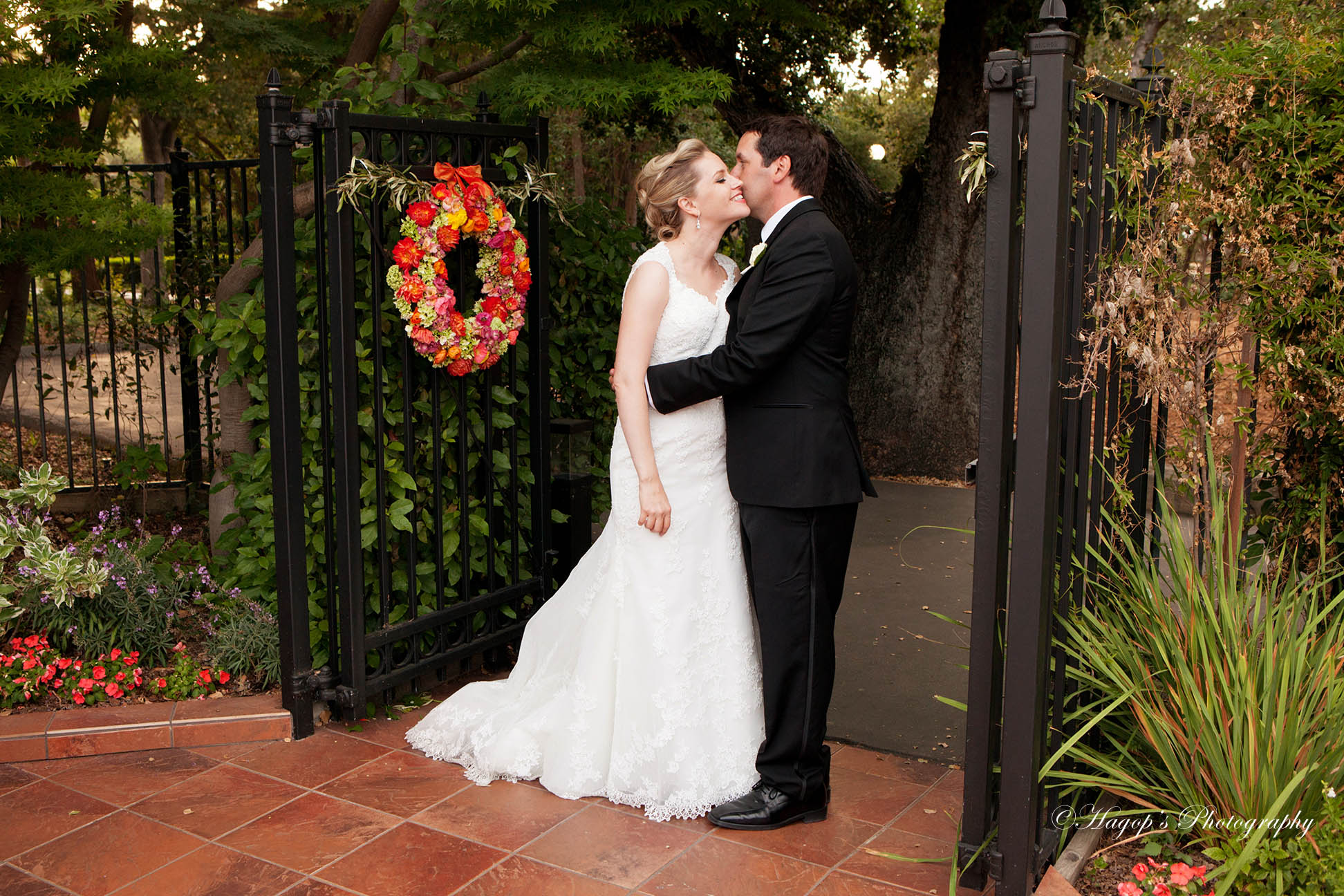 groom kissing the bride by the gate